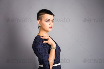 Portrait of young beautiful woman with stylish short haircut over grey background