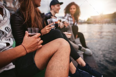 Group of people sitting on pier and having drinks