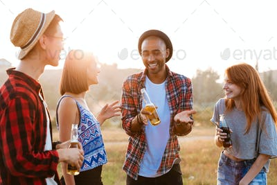 Cheerful young people with beer and soda talking outdoors