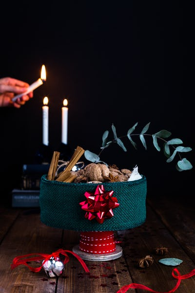 Festive Tin Filled with Nuts on Rustic Table against Candlelit Background