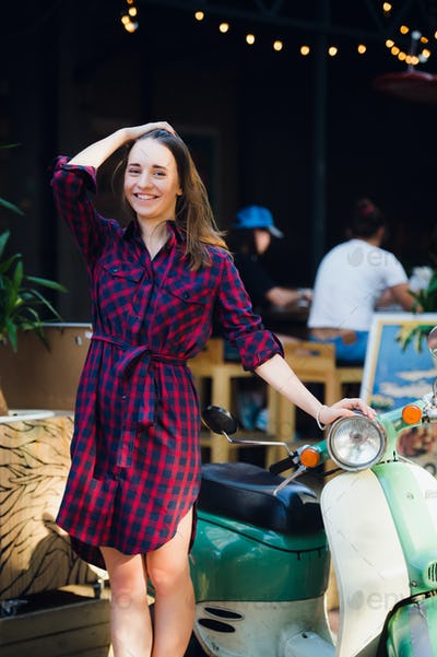 Urban fashion. Outdoor portrait of pretty young woman wearing checkered dress standing near scooter