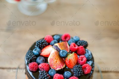 Cake with chocolate and berries. Studio shot, wooden background.