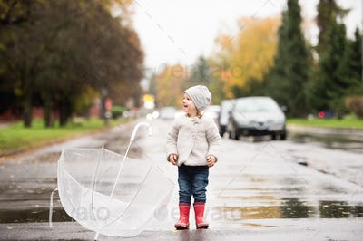 Little girl with transparent umbrella outside, rainy day.