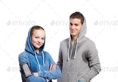 Teenage boy and girl in sweatshirts. Studio shot, isolated.