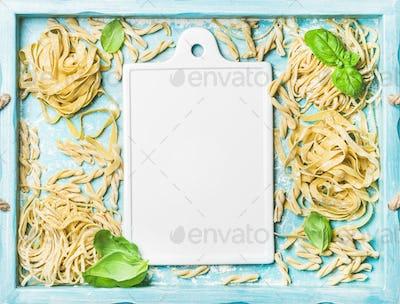 Various homemade fresh uncooked Italian pasta and white ceramic board