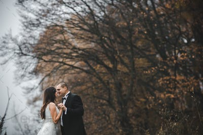 happy bride and groom posing in the autumn forest
