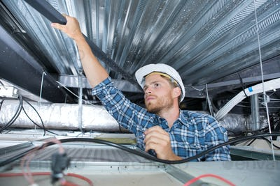 a craftsman wiring in the ceiling