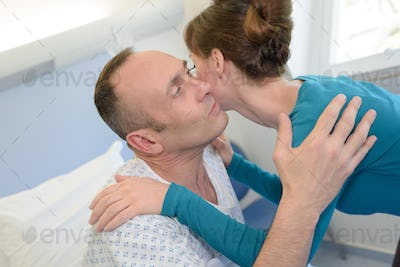 young man lying in bed at hospital and wife kissing