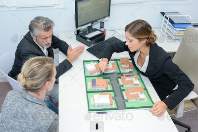 agent and couple discussing real estate contract top view