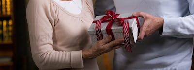 Elderly couple holding wrapped gift
