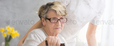 Elderly woman with hand on cane