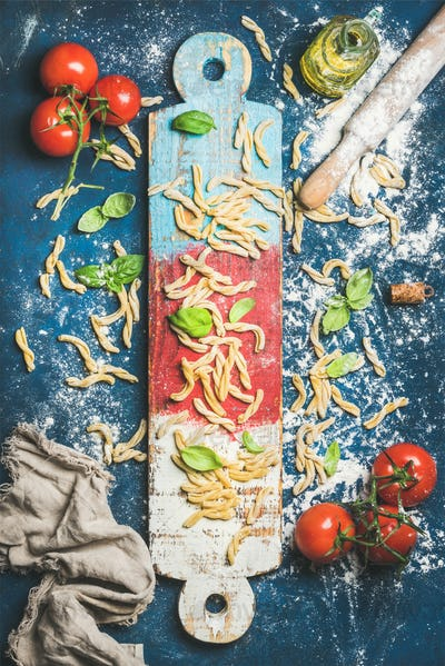 Italian casarecce, cherry-tomatoes, basil leaves and olive oil on board