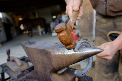 blacksmith forges a horseshoe hammering glowing steel