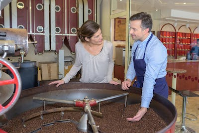 employees testing coffee quality during roasting at factory