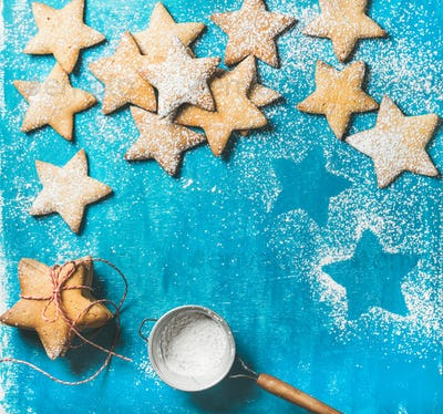Christmas gingerbread cookies with sugar powder on blue background