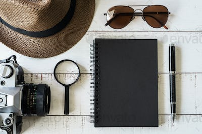 Black notebook with copyspace and retro camera on wooden background