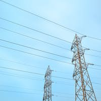 Two transmission towers, also known as electricity pylons.