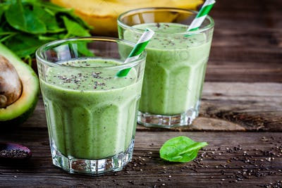 healthy green smoothie with banana, kiwi, avocado, spinach and chia seeds in glass