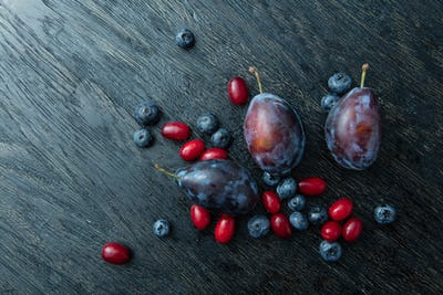 Fresh plums on a dark wooden table