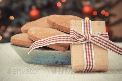 Vintage photo, Wrapped gift, gingerbreads and christmas tree with lights in background