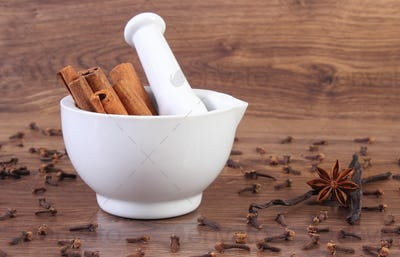 Fragrant cinnamon sticks in mortar and spices on rustic board
