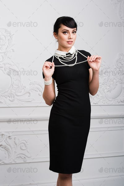 Beautiful retro woman with pearls necklace at luxury interior