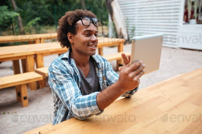 Cheerful african young man using tablet outdoors