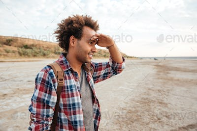 Concentrated african man standing outdoors and looking far away