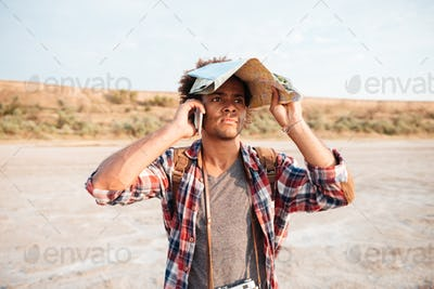 Man covered head with map and talking on mobile phone