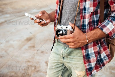 Man holding vintage photo camera and using mobile phone