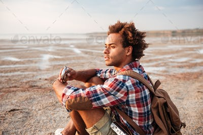Pensive man with backpack sitting and drinking from hip flask