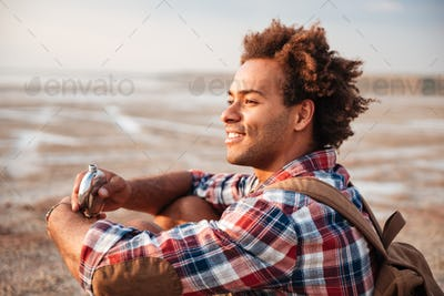 Smiling man with backpack drinking from hip flask on beach