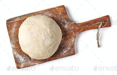fresh raw dough on wooden board