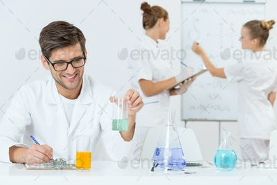 Young scientist writing down his findings