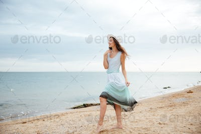 Woman in white hat and dress walking on the beach
