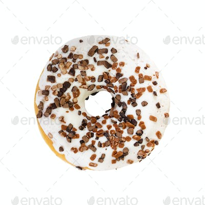 Donut with white icing and chocolate decorations. Top view.