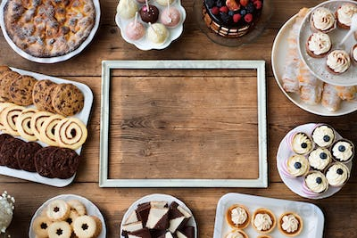 Picture frame and cakes, cookies, cakepops, cupcakes. Copy space.
