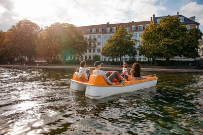 Young men and women boating in lake
