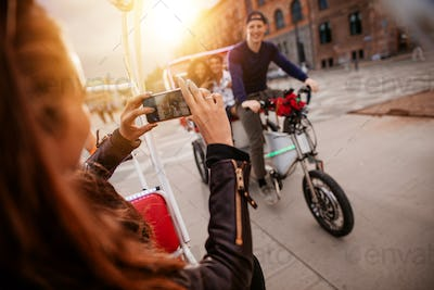 Woman taking picture of friends on tricycle