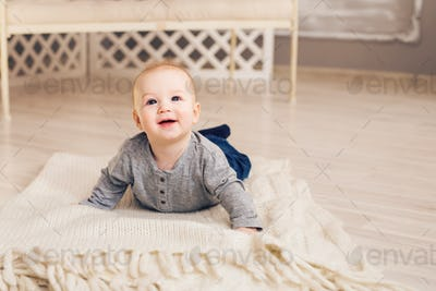 Adorable baby boy in sunny bedroom