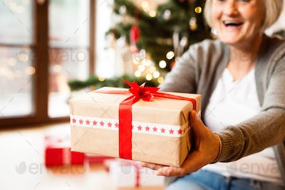 Unrecognizable senior woman in front of Christmas tree giving gift.