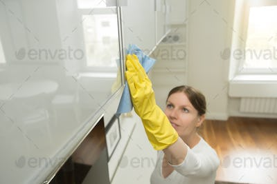 Young attractive woman cleaning an upper surface of kitchen clos