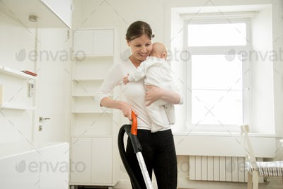 Smiling woman cleaning the carpet holding a baby