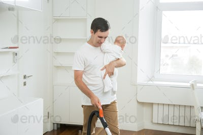 Frustrated stay-at-home dad vacuum cleaning the carpet holding a