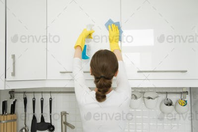 Rear view at young woman cleaning white kitchen wall cabinet