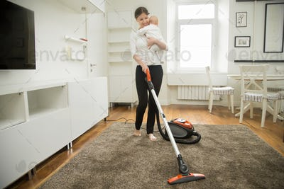 Happy smiling woman cleaning the carpet holding a child