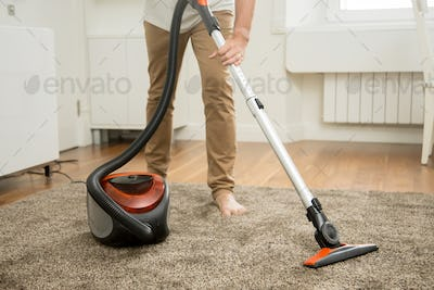 Close up of man vacuum cleaning the carpet
