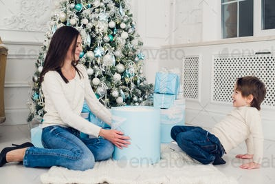 Woman and boy checking christmas presents at home