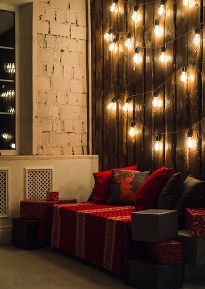 Wooden room in rustic house with wall and designer light bulbs, decorated place for seat. Red gray