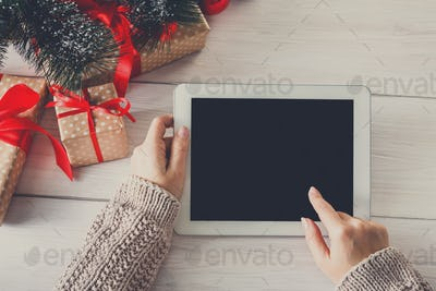 Woman christmas shopping online with tablet device